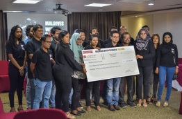 Staff of Raajje TV pose with a check of over MVR 5 million raised by the station to relieve the plight of the Rohingya. PHOTO: HUSSAIN WAHEED/MIHAARU