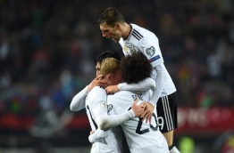 (L-R) Germany's midfielder Emre Can celebrates after scoring the fifth goal for Germany with his teammates midfielder Julian Brandt, midfielder Leroy Sane and midfielder Leon Goretzka during the FIFA World Cup 2018 qualification football match between Germany and Azerbaijan in Mainz, western Germany, on October 8, 2017. / AFP PHOTO / Christof STACHE