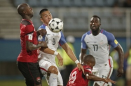 Trinidad and Tobago's Daneil Cyrus (L) and USA's Bobby Wood vie for the ball during their 2018 World Cup qualifier football match in Couva, Trinidad and Tobago, on October 10, 2017. / AFP PHOTO / Abraham Diaz