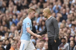 Manchester City's Belgian midfielder Kevin De Bruyne (L) walks by Manchester City's Spanish manager Pep Guardiola (R) as he is substituted during the English Premier League football match between Manchester City and Stoke City at the Etihad Stadium in Manchester, north west England, on October 14, 2017. / AFP PHOTO / Oli SCARFF / RESTRICTED TO EDITORIAL USE. No use with unauthorized audio, video, data, fixture lists, club/league logos or 'live' services. Online in-match use limited to 75 images, no video emulation. No use in betting, games or single club/league/player publications. /
