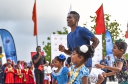 Hassan Saaid enjoys a friendly race with children at the Sports Stars Fiesta in Maafushi. PHOTO: HUSSAIN WAHEED/MIHAARU