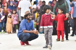 Kuda Ibbe watches as children sing at the Sports Stars Fiesta at Maafushi. PHOTO: HUSSAIN WAHEED/MIHAARU