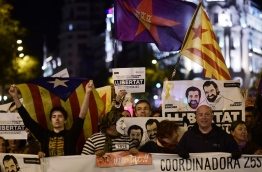"""Demonstrators hold posters demanding """"Freedom for political prisoners"""" with pictures of detained leaders of Catalan separatist groups Jordi Cuixart and Jordi Sanchez during a demonstration called by Coordinadora 25S in favour of the Catalan Republic and under the motto """"Goodbye mafia, hello Republic"""" in Madrid on November 5, 2017. / AFP PHOTO / Rafa RIVAS"""