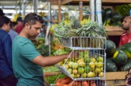 Man at a fruit stall in the Travellers' Market, Male. PHOTO: NISHAN ALI/MIHAARU