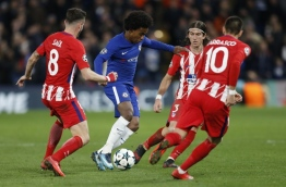 Chelsea's Brazilian midfielder Willian (C) is marked by Atletico Madrid's Spanish midfielder Saul Niguez (L) and Atletico Madrid's Brazilian defender Filipe Luis during a UEFA Champions League Group C football match between Chelsea and Atletico Madrid at Stamford Bridge in London on December 5, 2017. / AFP PHOTO / Ian KINGTON