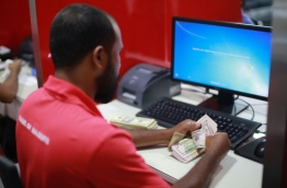 An employee of BML pictured counting US Dollars.
