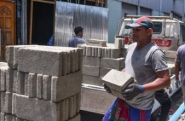 An expatriate worker carries cement bricks to a construction site. PHOTO/MIHAARU
