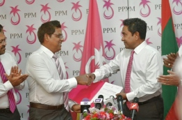Moosa Manik (L) shakes hands with President Abdulla Yameen after signing into PPM. FILE PHOTO/MIHAARU