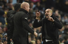Manchester City's Spanish manager Pep Guardiola (R) gestures to Burnley's English manager Sean Dyche (L) during the English FA Cup third round football match between Manchester City and Burnley at Etihad Stadium in Manchester, north west England on January 6, 2018. / AFP PHOTO / Oli SCARFF / RESTRICTED TO EDITORIAL USE. No use with unauthorized audio, video, data, fixture lists, club/league logos or 'live' services. Online in-match use limited to 75 images, no video emulation. No use in betting, games or single club/league/player publications. /