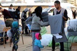Illegal immigrants receive blankets at a naval base in the Libyan capital Tripoli January 7, 2018, after they were rescued off the coast of Garabulli, 60 kilometres (40 miles) east of the capital. / AFP PHOTO / MAHMUD TURKIA