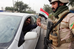 An Iraqi man gives a soldier a national flag at a checkpoint in the capital Baghdad on January 6, 2018, during festivities marking Iraq's Army Day. / AFP PHOTO / SABAH ARAR