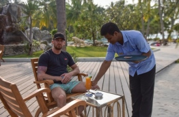 An employee of Sun Island Resort serves a drink to a tourist. PHOTO: HUSSAIN WAHEED/MIHAARU