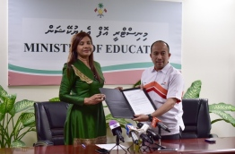 Education minister Dr Aishath Shiham (L) and EMGC's CEO Naudheen Thaajudheen pose for picture with agreement offering 500 higher education scholarships from Malaysia to the Maldives. PHOTO: HUSSAIN WAHEED/MIHAARU
