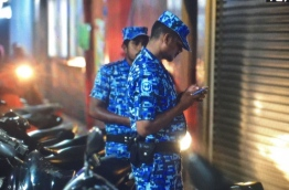 Two police officers wait outside a building in the capital Male while a team of police officers searched an apartment in the building on January 30, 2018, in relation to an incident encouraging paedophilia online. MIHAARU PHOTO / NISHAN ALI