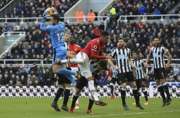 Newcastle United's Slovak goalkeeper Martin Dubravka (L) claims the ball in front of Manchester United's English defender Chris Smalling (C) during the English Premier League football match between Newcastle United and Manchester United at St James' Park in Newcastle-upon-Tyne, north east England on February 11, 2018. / AFP PHOTO / Lindsey PARNABY / RESTRICTED TO EDITORIAL USE. No use with unauthorized audio, video, data, fixture lists, club/league logos or 'live' services. Online in-match use limited to 75 images, no video emulation. No use in betting, games or single club/league/player publications. /