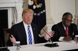 US President Donald Trump takes part in a meeting on infrastructure with state and local officials in the State Dining Room of the White House on February 12, 2018 in Washington, DC. At right is Vicksburg, Mississippi, Mayor George Flaggs. / AFP PHOTO / Mandel NGAN