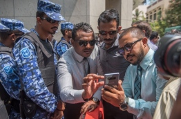 Thinadhoo-South MP Abdullah Mohamed (L) and Madduvari MP Mohamed Ameeth surrounded by riot police at a protest near the parliament. MIHAARU PHOTO / NISHAN ALI