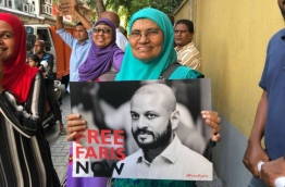 Former President Mohamed Nasheed's mother pictured holding a poster calling for the release of former President Maumoon Abdul Gayoom's son, Faris, during the opposition rally on March 2, 2018. PHOTO/SOCIAL MEDIA