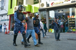 Riot police officers taking an opposition activist away from the crowds gathered at different parts of capital Male's main road Majeedhee Magu on March 2, 2018. MIHAARU PHOTO / HUSSEN WAHEED