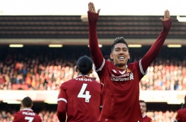 Liverpool's Brazilian midfielder Roberto Firmino celebrates scoring the team's third goal during the English Premier League football match between Liverpool and West Ham United at Anfield in Liverpool, north west England on February 24, 2018. / AFP PHOTO / Oli SCARFF / RESTRICTED TO EDITORIAL USE. No use with unauthorized audio, video, data, fixture lists, club/league logos or 'live' services. Online in-match use limited to 75 images, no video emulation. No use in betting, games or single club/league/player publications. /
