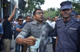 Police taking Mahloof aside from a rally. PHOTO/ALI NISHAN/MIHAARU