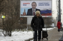 "(FILES) In this file photo taken on January 12, 2018 people pass by a billboard with an image of Russia's President Vladimir Putin and lettering ""Strong president - Strong Russia!"" in Saint Petersburg. / AFP PHOTO / Olga MALTSEVA"
