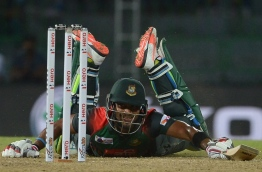 Bangladesh cricketer Sabbir Rahman successfully dives and avoids being run out during the Fifth Match, Nidahas Twenty20 Tri-Series international cricket match between India and Bangladesh at the R. Premadasa stadium in Colombo on March 14, 2018. / AFP PHOTO / LAKRUWAN WANNIARACHCHI