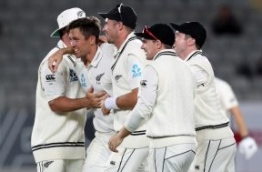 New Zealand's Trent Boult (L) celebrates with Tim Southee (C) and teammates after taking the wicket of England's Joe Root on the fourth day of the day-night Test cricket match between New Zealand and England at Eden Park in Auckland on March 25, 2018. / AFP PHOTO / Michael BRADLEY