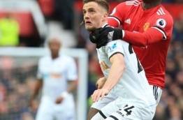 Swansea City's Scottish midfielder Adam King (L) vies with Manchester United's French midfielder Paul Pogba during the English Premier League football match between Manchester United and Swansea at Old Trafford in Manchester, north west England, on March 31, 2018. / AFP PHOTO / Lindsey PARNABY / RESTRICTED TO EDITORIAL USE. No use with unauthorized audio, video, data, fixture lists, club/league logos or 'live' services. Online in-match use limited to 75 images, no video emulation. No use in betting, games or single club/league/player publications. /