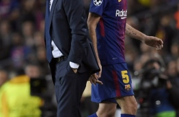 Barcelona's Spanish midfielder Sergio Busquets (R) walks past Barcelona's Spanish coach Ernesto Valverde as he leaves the pitch during the UEFA Champions League quarter-final first leg football match between FC Barcelona and AS Roma at the Camp Nou Stadium in Barcelona on April 4, 2018. / AFP PHOTO / LLUIS GENE