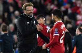 Liverpool's German manager Jurgen Klopp (L) gestures with Liverpool's English midfielder Alex Oxlade-Chamberlain at the final whistle during the UEFA Champions League first leg quarter-final football match between Liverpool and Manchester City, at Anfield stadium in Liverpool, north west England on April 4, 2018. / AFP PHOTO / Anthony Devlin