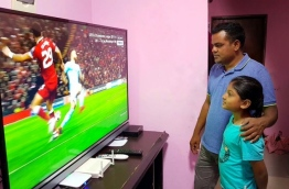 A man and a child watch Dhiraagu TV after its launching in GA. Villingili. PHOTO/MIHAARU