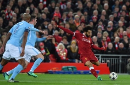 Liverpool's Egyptian midfielder Mohamed Salah takes a shot during the UEFA Champions League first leg quarter-final football match between Liverpool and Manchester City, at Anfield stadium in Liverpool, north west England on April 4, 2018. / AFP PHOTO / Anthony Devlin