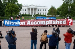 """US President Donald Trump on April 15, 2018, defended his having hailed a US and allied strike in Syria as """"Mission Accomplished."""" The phrase immediately evoked former president George W. Bush's premature Iraq victory speech on board the aircraft carrier USS Abraham Lincoln on May 1, 2003. A banner proclaiming """"Mission Accomplished"""" loomed in the background as Bush declared the end of major combat operations in Iraq, a claim belied by the years of hard fighting that followed. / AFP PHOTO / Paul J. RICHARDS"""