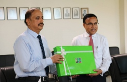 Pakistan's Ambassador for Maldives Waseem (L) gifting the 30 laptops. State minister for Education Dr.Nazeer accepting the gifts on behalf of the ministry. PHOTO/EDUCATION MINISTRY