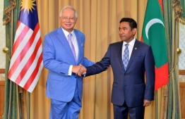 President Yameen Abdul Gayoom (R) shakes hands with outgoing Malaysia PM Najib Razak
