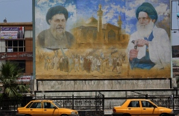 A poster shows Shiite leader Moqtada al-Sadr (L) and cleric Mohammed Baqer al-Sadr in Sadr City, east of the Iraqi capital Baghdad on May 14, 2018. In the impoverished stronghold of Iraqi cleric Moqtada Sadr in Baghdad, supporters of the Shiite populist are hopeful for improvements as results put him on top in parliament elections.  / AFP PHOTO / AHMAD AL-RUBAYE