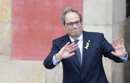 The new elected Catalan regional president Quim Torra waves as he leaves the Catalan parliament after his election during a parliamentary vote session in Barcelona on May 14, 2018. Quim Torra, a newcomer to politics who has long fiercely campaigned for independence in Catalonia, was appointed regional president today, vowing to keep fighting for an independent republic.       / AFP PHOTO / LLUIS GENE