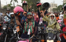 In this picture taken on May 13, 2018, Pakistani women celebrate as they ride pink motorcycles during the pink motorcycles rally in Lahore. Punjab government launched a Pink Motorcycle Scheme with the aim to empower women in society. / AFP PHOTO / ARIF ALI