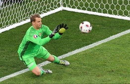 (FILES) In this file photo taken on July 7, 2016, Germany's goalkeeper Manuel Neuer stops the ball by France's forward Dimitri Payet (not pictured) during the Euro 2016 semi-final football match between Germany and France at the Stade Velodrome in Marseille. Injured Manuel Neuer was named on May 15, 2018 in Germany's 27-man World Cup squad for the 2018 FIFA Football World Cup. / AFP PHOTO / BORIS HORVAT