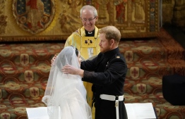 Britain's Prince Harry, Duke of Sussex (R) removes the veil of US actress Meghan Markle (L) as they stand at the altar together before Archbishop of Canterbury Justin Welby (C) in St George's Chapel, Windsor Castle, in Windsor, on May 19, 2018 during their wedding ceremony. / AFP PHOTO / POOL / Owen Humphreys