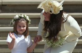 Princess Charlotte (L) waves by her mother Britain's Catherine, Duchess of Cambridge after attending the wedding ceremony of Britain's Prince Harry, Duke of Sussex and US actress Meghan Markle at St George's Chapel, Windsor Castle, in Windsor, on May 19, 2018. / AFP PHOTO / POOL / Jane Barlow