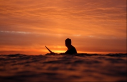 A surfer waits to catch the last wave of the day.  PHOTO BY SARAH HALEEM @sarahhaleemphotography on FACEBOOK