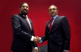 Qasim Ibrahim (L) and Dr. Mohamed Jameel shake hands during a meeting in Germany.