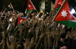Protesters raise their hands and wave flags near members of the gendarmerie and security forces during a demonstration outside the prime minister's office in the capital Amman late on June 3, 2018. Jordan's senate met on June 3 for a special session after another night of protests across the country against IMF-backed austerity measures including a draft income tax law and price hikes. Some 3,000 people faced down a heavy security presence to gather near the prime minister's office in Amman until the early hours of Sunday morning. / AFP PHOTO / Khalil MAZRAAWI