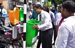 Environment Minister Thoriq Ibrahim placing a dustbin in Chaandhanee Magu to kick off the Road Side Dustbin Pilot Project 2018. PHOTO/AHMED NISHAATH