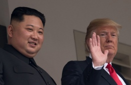 US President Donald Trump (R) waves as he and North Korea's leader Kim Jong Un look on from a veranda during their historic US-North Korea summit, at the Capella Hotel on Sentosa island in Singapore on June 12, 2018. Donald Trump and Kim Jong Un have become on June 12 the first sitting US and North Korean leaders to meet, shake hands and negotiate to end a decades-old nuclear stand-off. / AFP PHOTO / SAUL LOEB