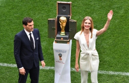 Russian model Natalia Vodianova (R) and Spanish goalkeeper Iker Casillas stand next to the World Cup trophy during the opening ceremony before the Russia 2018 World Cup Group A football match between Russia and Saudi Arabia at the Luzhniki Stadium in Moscow on June 14, 2018. / AFP PHOTO / Mladen ANTONOV /