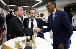 Russian Prime Minister Dmitry Medvedev (L) shakes hands with Rwanda's President Paul Kagame as French former president Nicolas Sarkozy stands nearby before the opening ceremony prior to the Russia 2018 World Cup Group A football match between Russia and Saudi Arabia at the Luzhniki Stadium in Moscow on June 14, 2018. / AFP PHOTO / SPUTNIK / Dmitry ASTAKHOV