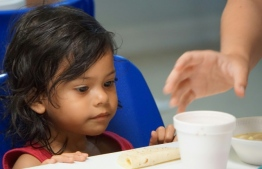 A young girl looks at a cup of soup handed to her by volunteers in a migration center in the border town of McAllen, Texas - Image: AFP